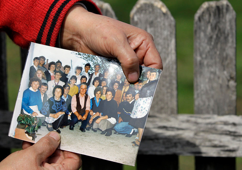 . A  woman displays Ljubisa Bogdanovic, top row third right, with her left thumb in a  group picture in the village of Velika Ivanca, Serbia, Tuesday, April 9, 2013. The 60-year-old man gunned down 13 people, including a baby, in a house-to-house rampage in the quiet village on Tuesday before trying to kill himself and his wife, police and hospital officials said. Belgrade emergency hospital spokeswoman Nada Macura said the man, identified as Ljubisa Bogdanovic, used a handgun in the shooting spree at five houses. The dead included six women. (AP Photo/Darko Vojinovic)