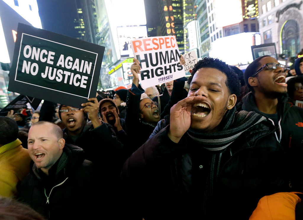 . Protestors shout at Times Square after it was announced that the New York City police officer involved in the death of Eric Garner is not being indicted, Wednesday, Dec. 3, 2014, in New York. A grand jury cleared the white New York City police officer Wednesday in the videotaped chokehold death of Garner, an unarmed black man, who had been stopped on suspicion of selling loose, untaxed cigarettes, a lawyer for the victim\'s family said. A video shot by an onlooker and widely viewed on the Internet showed the 43-year-old Garner telling a group of police officers to leave him alone as they tried to arrest him. The city medical examiner ruled Garner\'s death a homicide and found that a chokehold contributed to it. (AP Photo/Julio Cortez)