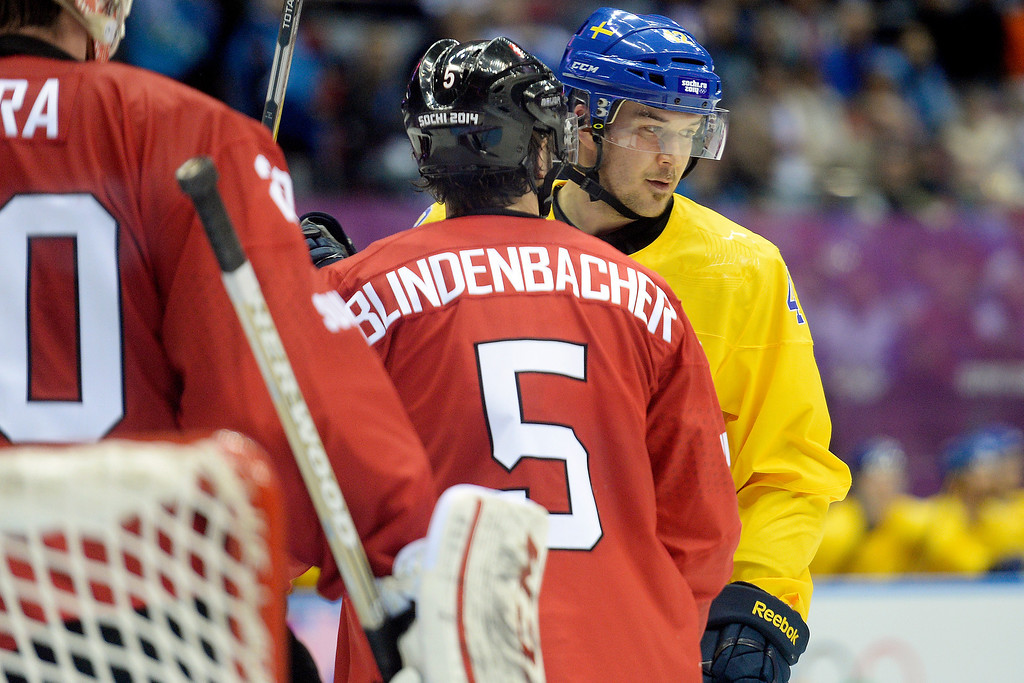 . Sweden\'s Jimmie Ericsson and Switzerland\'s Seeverin Blindenbacher mix it up inside the crease during the action at Bolshoy Arena. Sochi 2014 Winter Olympics on Friday, February 14, 2014. (Photo by AAron Ontiveroz/The Denver Post)