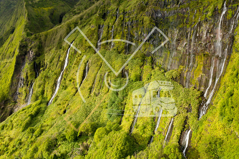 aerial landscape image of sunset sunrise over Poço Ribeira do Ferreiro waterfalls with its remarkable amazing tropical like green vegetation and forests at the Ilha das Flores island on the Azores