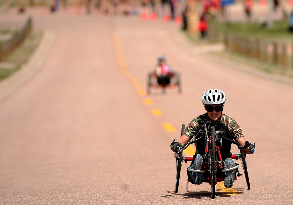 . Elizabeth Wasil, with the Army, works hard to get up the hill during the Women\'s 10K Handcycle and Recumbent race.  The fourth annual Warrior Games cycling event took started and finished at Falcon Stadium on the grounds of the Air Force Academy in Colorado Springs, CO on May 12, 2013.  HRH Prince Harry was on hand to start the race as well as to hand out medals at the finish line.   A total of 260 wounded, ill and injured service members and veterans came to compete in the week long games.  Members of the Army, Marine Corps, Navy/Coast Guard/Air Force. Special Operations and the British Armed Forces all took part in the competition.  Other events included in the Warrior Games are shooting, sitting volleyball, track & field and wheelchair basketball.  (Photo by Helen H. Richardson/The Denver Post)