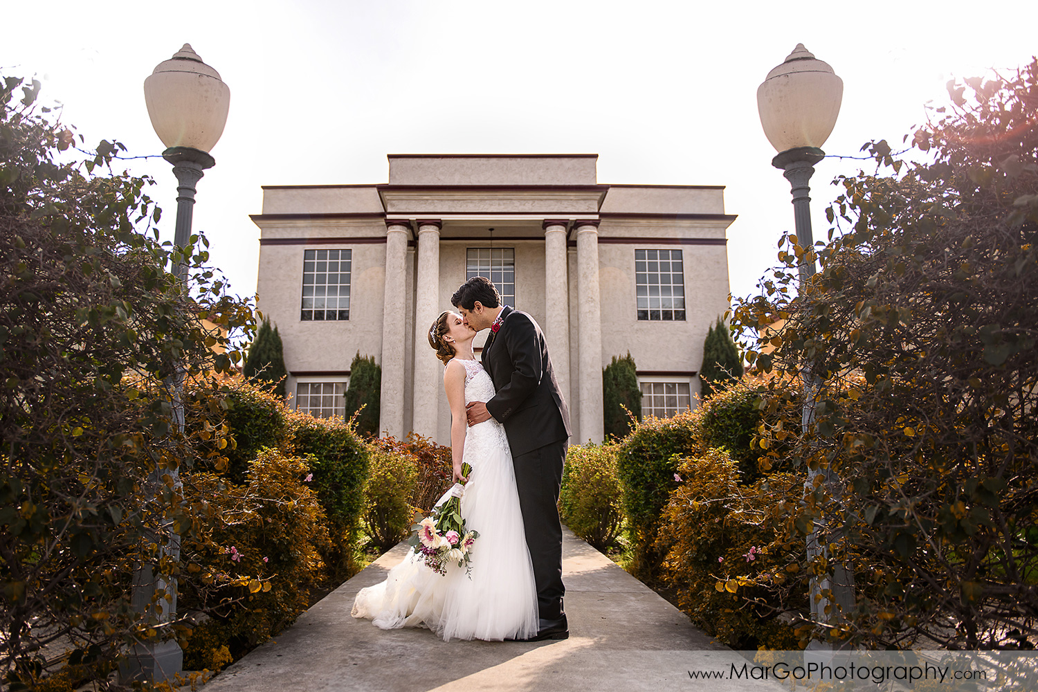 bride and groom kissing in front of Fremont Century House & Gardens