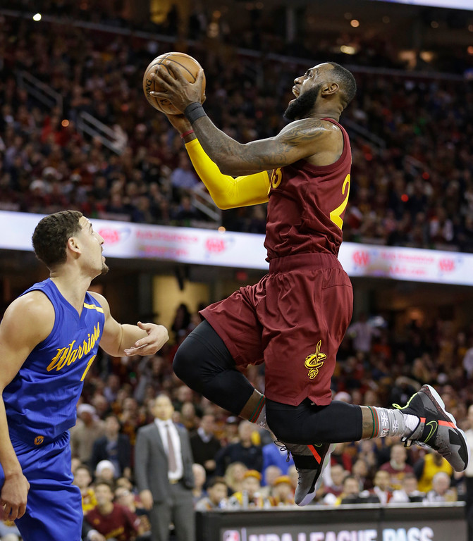 . Cleveland Cavaliers\' LeBron James, right, drives to the basket against Golden State Warriors\' Klay Thompson in the first half of an NBA basketball game, Sunday, Dec. 25, 2016, in Cleveland. (AP Photo/Tony Dejak)