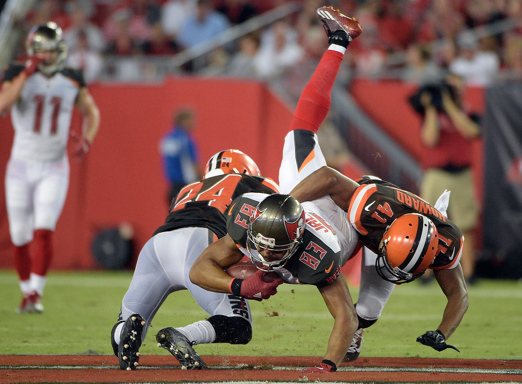. Cleveland Browns defensive back Ibraheim Campbell (24) and cornerback Tracy Howard (41) take down Tampa Bay Buccaneers wide receiver Vincent Jackson during the third quarter of an NFL preseason football game Friday, Aug. 26, 2016, in Tampa, Fla. (AP Photo/Phelan M. Ebenhack)