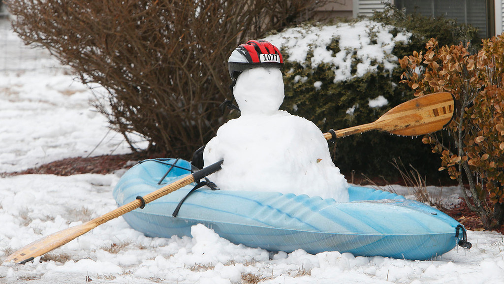 . A kayak snowman is seen in the front yard of a house on U.S. Highway 35, Wednesday, Feb. 12, 2014, in Fort Payne, Ala. Trees and limbs began snapping under the weight of a coat of ice in east Alabama Wednesday, blocking roads during a winter storm that forecasters said could leave as much as a foot of snow in the Tennessee Valley. (AP Photo/Hal Yeager)