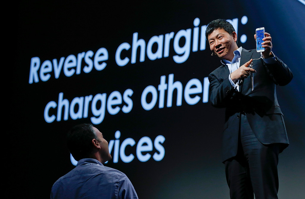 . Huawei Consumer Business Group CEO Richard Yu demonstrates the Ascend Mate 2 smartphone\'s ability to charge other devices during the International Consumer Electronics Show, Monday, Jan. 6, 2014, in Las Vegas. (AP Photo/Julie Jacobson)