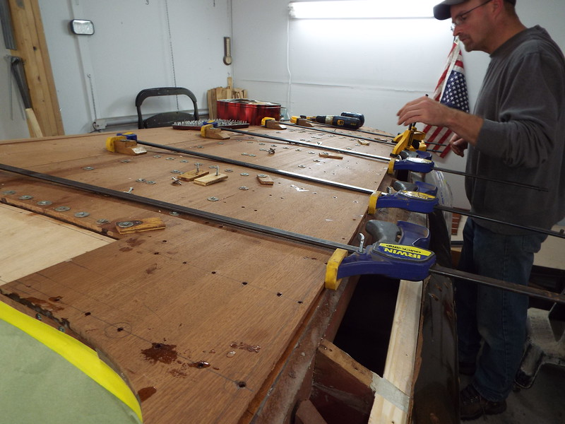 Setting the last port rear plank in place before holding it with temporary fasteners.