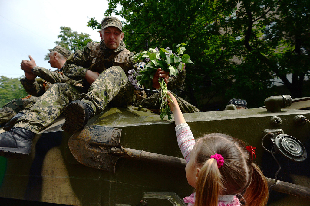 . Armed pro-Russian militants receive flowers from a young girl while taking part in a ceremony marking the 69 years since Soviet victory in World War II, in Slavyansk on May 9, 2014.     AFP PHOTO / VASILY MAXIMOV/AFP/Getty Images