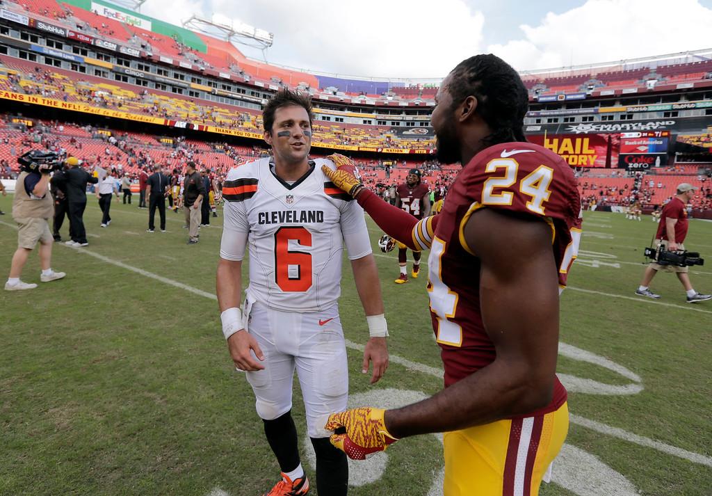 . Cleveland Browns quarterback Cody Kessler (6) and Washington Redskins cornerback Josh Norman (24) talk after an NFL football game Sunday, Oct. 2, 2016, in Landover, Md. The Redskins won 31-20. (AP Photo/Chuck Burton)