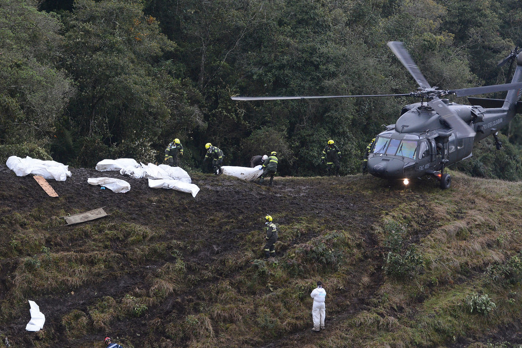. Rescue workers place the bodies of victims of an airplane crash into a waiting helicopter, in La Union, near Medellin, Colombia, Tuesday, Nov. 29, 2016. The chartered plane was carrying a Brazilian soccer team to the biggest match of its history when it crashed into a Colombian hillside and broke into pieces, killing 75 people and leaving six survivors, Colombian officials said Tuesday. (AP Photo/Luis Benavides)