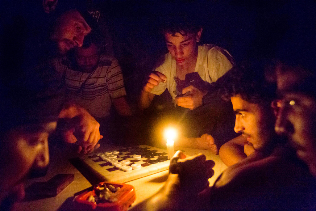 """. Syrian rebel fighters play a game by candle light, due to electricity cuts on May 26, 2013 in Adana, near the northeastern city of Deir Ezzor. Syria\'s opposition denounced as \""""too little, too late\"""" an EU decision to lift an arms embargo on rebels fighting the regime of President Bashar al-Assad. Ricardo Garcia Vilanova/AFP/Getty Images"""