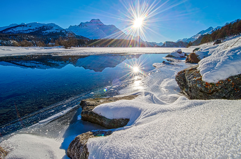 Frozen lake in snowy Swiss winter landscape on a sunny day