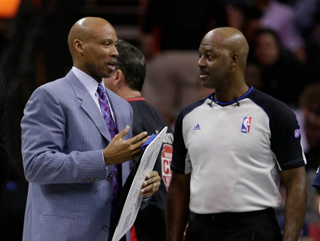 . Cleveland Cavaliers head coach Byron Scott, left, talks with referee Haywoode Workman, right, during the first half of an NBA basketball game against the Charlotte Bobcats in Charlotte, N.C., Wednesday, April 17, 2013. (AP Photo/Chuck Burton)