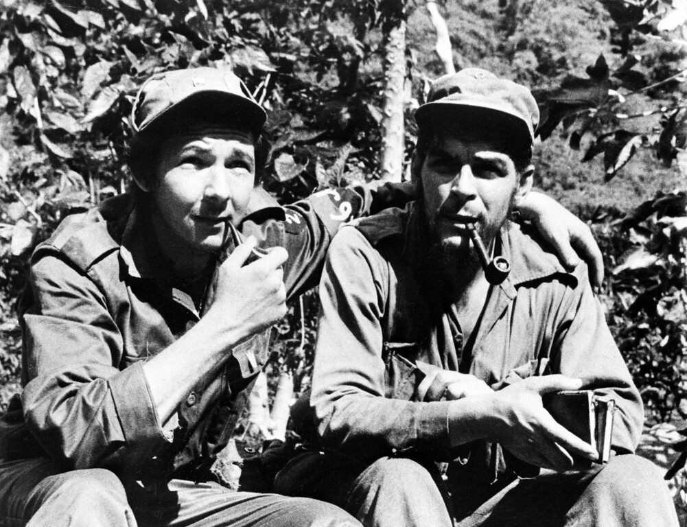 ". Raul Castro, left, younger brother to Cuban leader Fidel Castro, has his arm around second-in-command, Ernesto ""Che\"" Guevara, Argentine national, in their Sierra de Cristal mountain stronghold south of Havana, Cuba, during the Cuban revolution in June 26, 1958.  (AP Photo/Andrew St. George)"