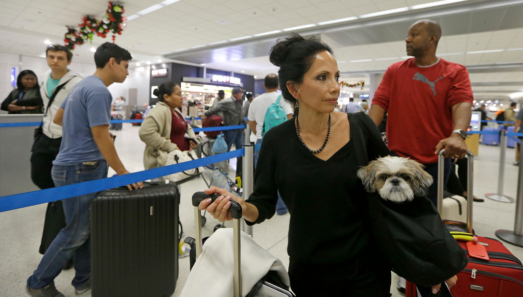 . Passenger Rebecca Alva with her pet Annie waits in line to check in her luggage on her way to New York to spend the Thanksgiving holiday with her relatives at Miami International Airport, Wednesday, Nov. 23, 2016, in Miami. Almost 49 million people are expected to travel 50 miles or more for the holiday, the most since 2007, according to AAA.  (AP Photo/Alan Diaz)