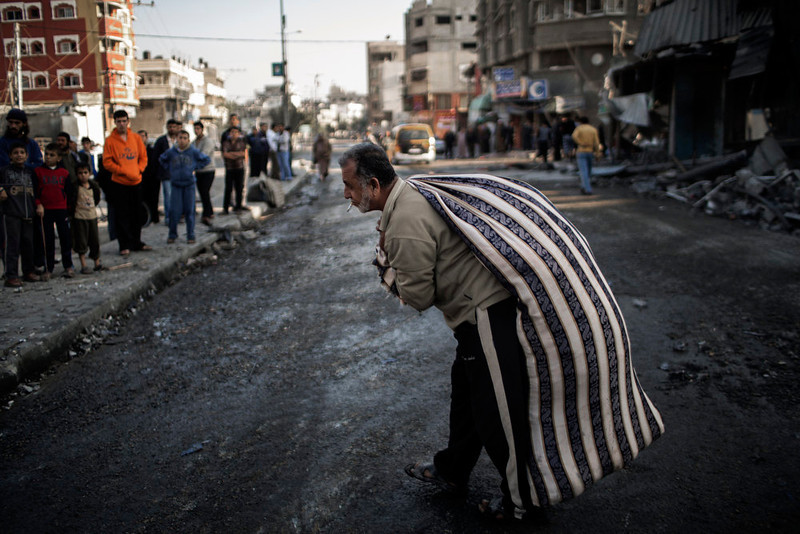 . A Palestinian carries a bag of salvaged items from a house destroyed in an Israeli airstrike on Gaza City, on November 20, 2012. Seven Palestinians were wounded in strikes on Gaza overnight, but no one was killed in the first night without fatalities since the Israeli air campaign began nearly a week ago. MARCO LONGARI/AFP/Getty Images