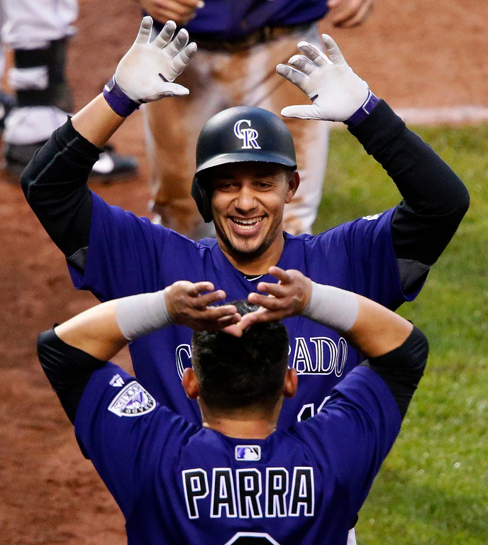 . Colorado Rockies\' Cristhian Adames, top, is greeted by teammate Gerardo Parra after hitting a two run home run off Pittsburgh Pirates relief pitcher Jared Hughes in the ninth inning of a baseball game in Pittsburgh, Saturday, May 21, 2016. The Rockies won 5-1. (AP Photo/Gene J. Puskar)