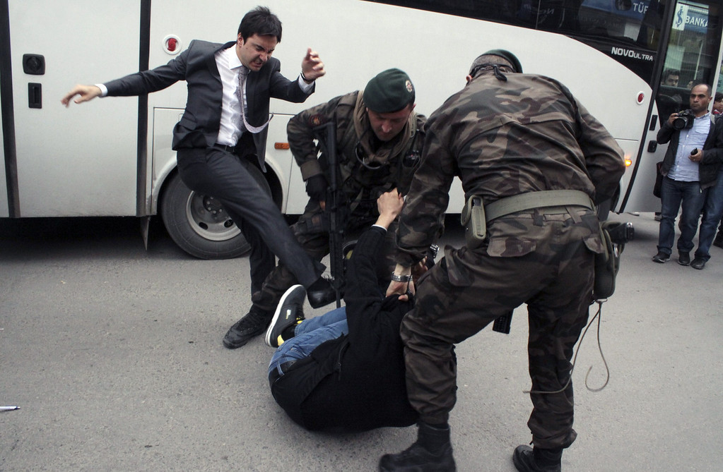 . Photo taken on May 14, 2014shows  a person identified by Turkish media as Yusuf Yerkel, advisor to Turkish Prime Minister Recep Tayyip Erdogan, kicking a protester already held by special forces police members during Erdogan\'s visit to Soma, Turkey. Erdogan was visiting the western Turkish mining town of Soma after Turkey\'s worst mining accident . DEPO PHOTOS/AFP/Getty Images