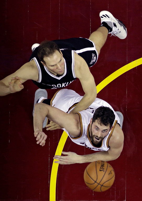 . Cleveland Cavaliers\' Kevin Love, bottom, and Brooklyn Nets\' Bojan Bogdanovic, top, battle for the ball in the first half of an NBA basketball game, Friday, Dec. 23, 2016, in Cleveland. (AP Photo/Tony Dejak)