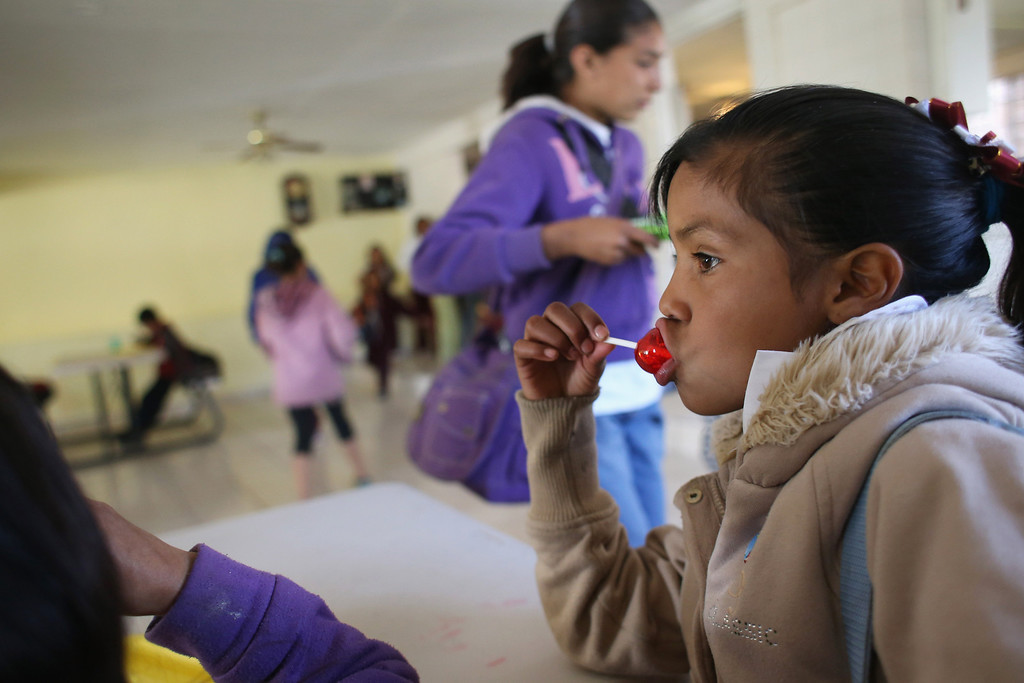 . NOGALES, MEXICO - MARCH 05:  Children receive a free lunch at the Home of Hope and Peace kitchen on March 5, 2013 in Nogales, Mexico. The non-profit organization feeds some 100 school children each day, many of whom\'s parents work at the nearby Tirabichi garbage dump, picking out recyclables for a living. Some of them were undocumented workers who were deported from the United States to Mexico.  (Photo by John Moore/Getty Images)