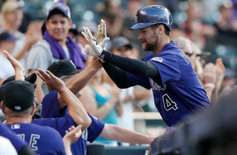 . Colorado Rockies pinch-hitter Ben Paulsen, right, is congratulated by teammates after hitting a two-run home run against the San Francisco Giants in the seventh inning of the Rockies\' 10-9 victory in a baseball game in Denver on Monday, Sept. 1, 2014. (AP Photo/David Zalubowski)