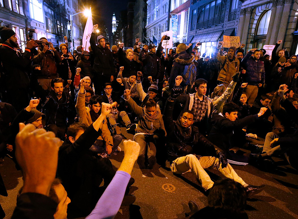 . A group of protesters rallying against a grand jury\'s decision not to indict the police officer involved in the death of Eric Garner stage a brief sit in at the corner of Broadway and Prince Street, Wednesday, Dec. 3, 2014, in New York. (AP Photo/Jason DeCrow)