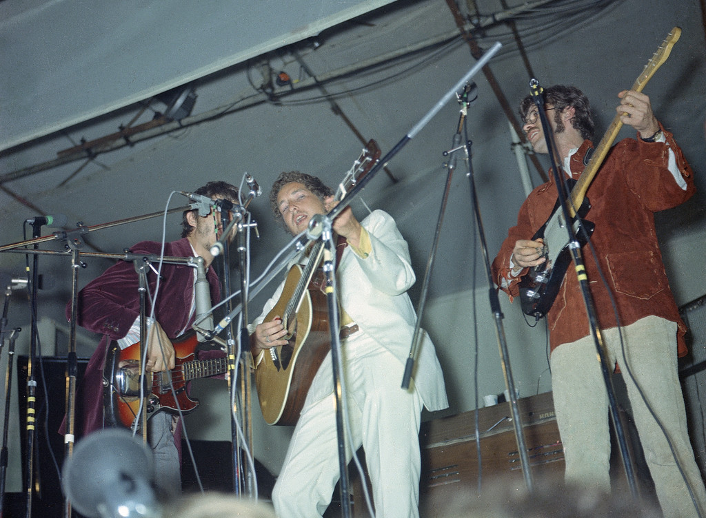 ". American folk singer Bob Dylan, center, performs with members of  ""The Band\"" Robbie Robertson, right and Rick Danko, left, during a three-day festival at Woodside Bay, Isle of Wight, England,  Aug. 31, 1969. The audience, estimated at 200,000 people, gathered on the 100-acre field (AP Photo)"