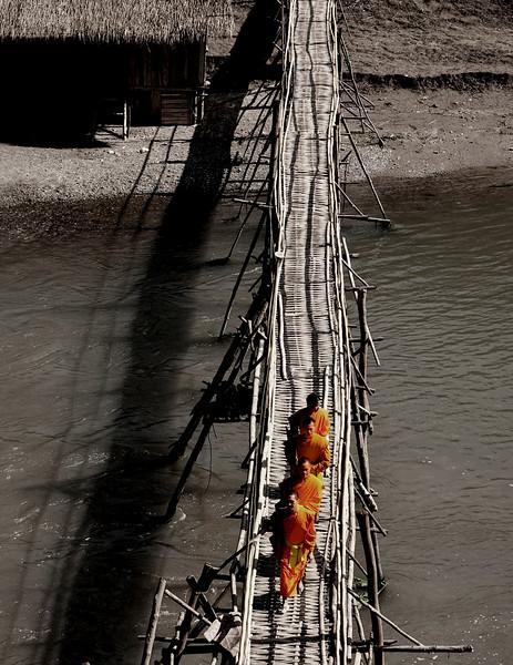 Monks crossing a Bamboo bridge.  Luang Prabang, Laos, 2010.