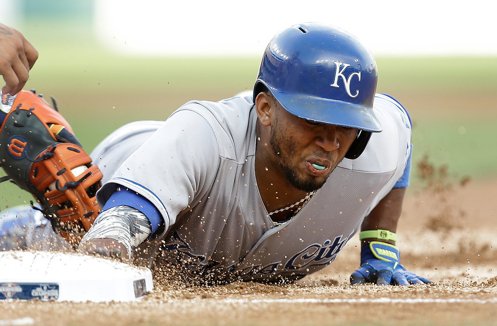 . Kansas City Royals\' Alcides Escobar dives back into first base safely under the tag of Detroit Tigers first baseman Miguel Cabrera in the second inning of a baseball game in Detroit, Tuesday, June 17, 2014.  (AP Photo/Paul Sancya)