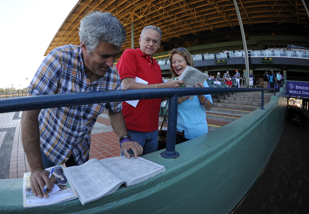 . Mark Batlin, left, looks over the racing program as Wright Batlin, center, and Kathy Parnello of Northern California look on prior to the Breeders\' Cup at Santa Anita Park in Arcadia, Calif., on Saturday, Nov. 2, 2013. 