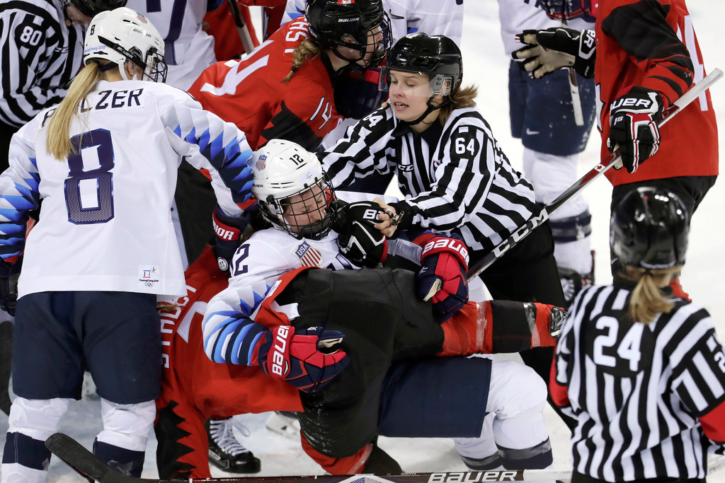 . Official Jenni Heikkinen (64), of Finland, tries to separate Kelly Pannek (12), of the United States, and Laura Stacey (7), of Canada, as they scuffle during the third period of a preliminary round during a women\'s hockey game at the 2018 Winter Olympics in Gangneung, South Korea, Thursday, Feb. 15, 2018. Canada won 2-1. (AP Photo/Julio Cortez)