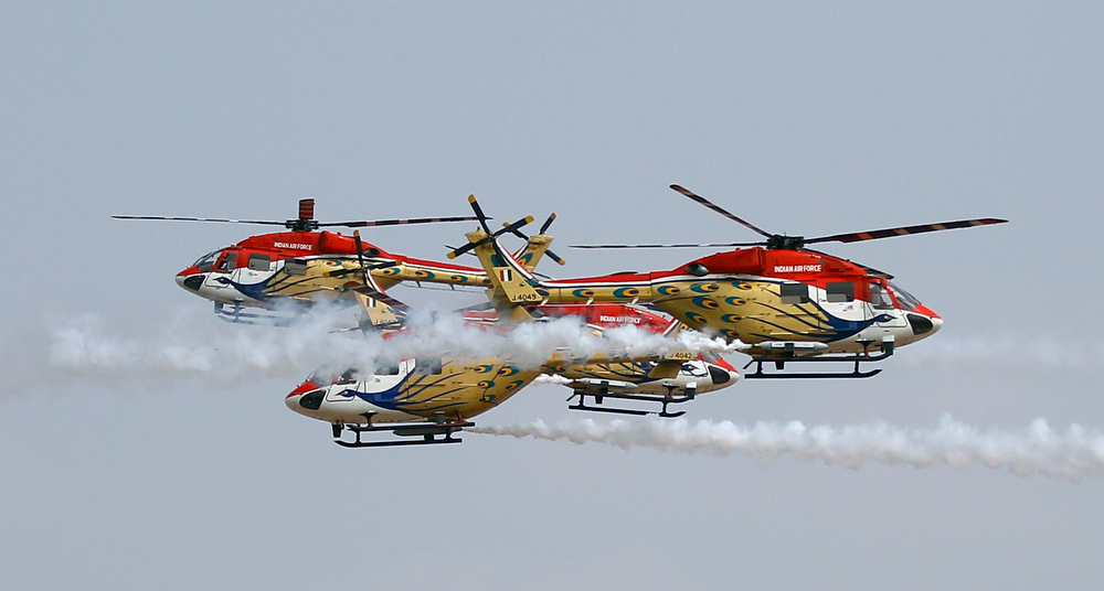 . Indian Air Force helicopters cross each other as they perform aerobatic flight on the third day of the Aero India 2013 at Yelahanka air base in Bangalore, India, Friday, Feb. 8, 2013. More than 600 aviation companies along with delegations from 78 countries are participating in the five-day event that started Wednesday. (AP Photo/Aijaz Rahi)