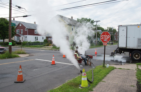 06/24/19 Wesley Bunnell | Staff Steam is piped from the sewers as a worker watches over the re lining efforts that are underway on a section of sewer at the corner of Belden St and Chapman St on Monday afternoon.