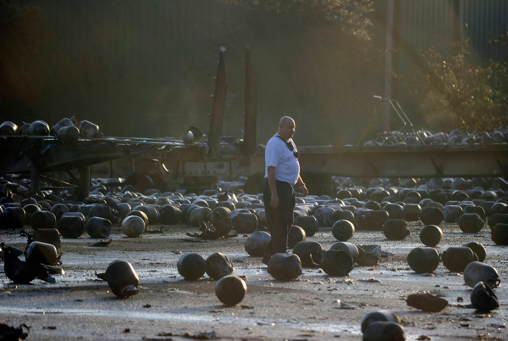 . A firefighter walks among exploded propane cylinders littering the storage yard of a propane plant following massive explosions overnight in the plant\'s yard, in Tavares, Florida, July 30, 2013. Dozens of explosions rocked a propane tank servicing plant in central Florida, northwest of Orlando, late on Monday, injuring seven workers, at least three critically, and prompting the evacuation of nearby homes, authorities said.   REUTERS/David Manning