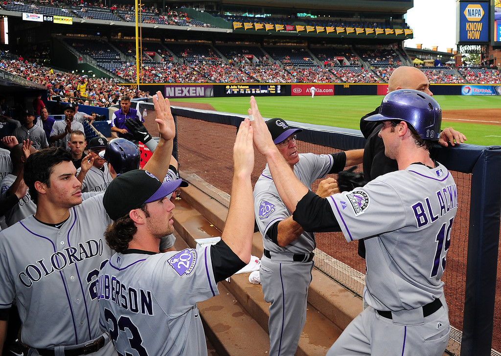 . Charlie Blackmon #19 of the Colorado Rockies is congratulated by teammates after scoring a second inning run against the Atlanta Braves at Turner Field on August 1, 2013 in Atlanta, Georgia. (Photo by Scott Cunningham/Getty Images)