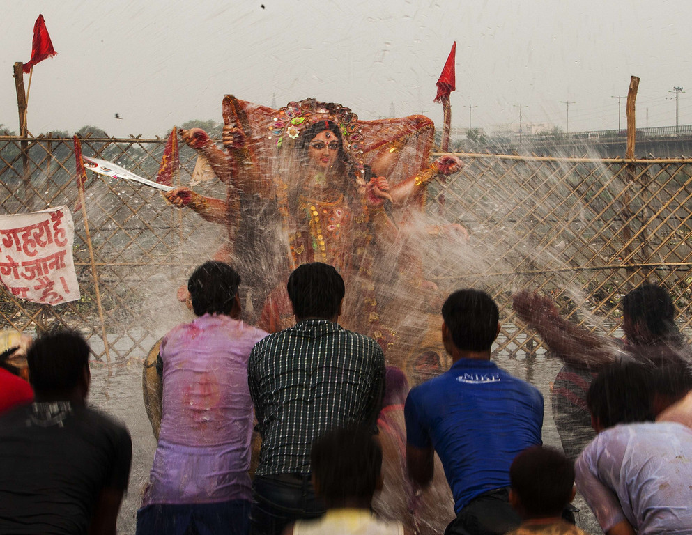 . Indian Hindu devotees splash water on an idol after it was immersed in the Yamuna river as part of the Durga Puja festival in New Delhi on October 13, 2013. Durga Puja commemorates the slaying of demon king Mahishasur by goddess Durga, marking the triumph of good over evil.    Andrew Caballero-Reynolds/AFP/Getty Images