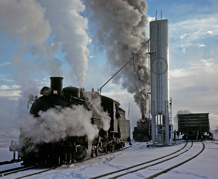 Early on a cold winter morning two engines are serviced.  The 480 is filling its sand dome and the 488 behind is loading coal from the Red Devil coal loader.  The relatively modern sanding tower was built out of an old tank car, note the round cutout where the dome once was. December 18, 1961.