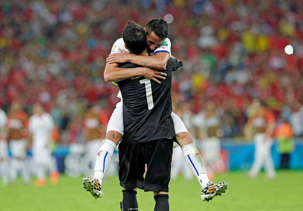 . Chile\'s goalkeeper Claudio Bravo is embraced by Mauricio Isla after the group B World Cup soccer match between Spain and Chile at the Maracana Stadium in Rio de Janeiro, Brazil, Wednesday, June 18, 2014. Defending champion Spain was eliminated from the World Cup after losing to Chile 2-0.  (AP Photo/Bernat Armangue)
