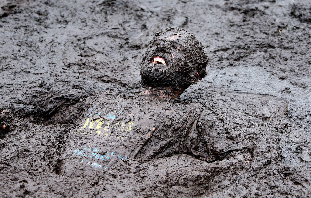 . A competitor competes in the Mud Madness race, at Foymore Lodge in Portadown, County Armagh on September 14, 2014. Some 800 Competitors ran, crawled and belly-flop their way across four and half miles of bogs and ponds, under cargo nets and through water sprays and muddy trenches in aid of Charity.    AFP PHOTO / Paul  FAITH/AFP/Getty Images