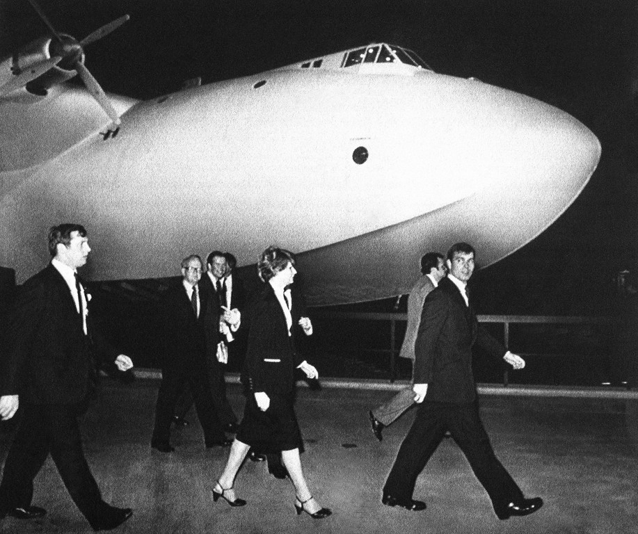. Prince Andrew, right, is escorted by an entourage as he visits the famed Howard Hughes flying machine, the Spruce Goose, in Long Beach, California on Monday, April 16, 1984. (AP Photo/Lennox McLendon)
