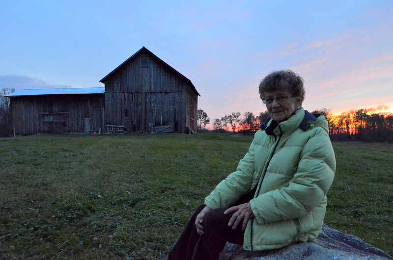 Mom next to the barn where she used to milk the cows before going to school.