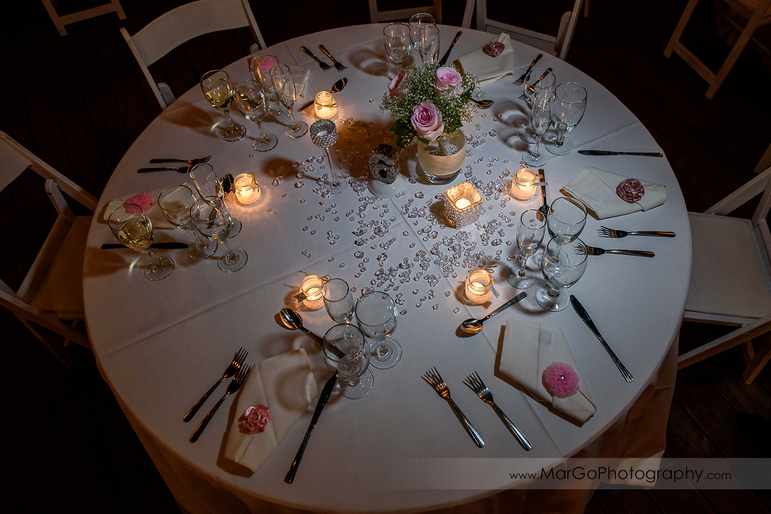 round wedding reception table decorated with pink flowers