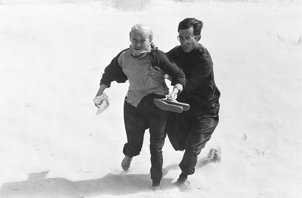 . A Roman Catholic priest aids an elderly villager to brave the windy rotor blast from a government helicopter as they run to board it from west of Tuy Hoa in Vietnam, Wednesday, March 27, 1975. They were among thousands of refugees from the Central Highlands who were picked up along the central coast. (AP Photo/Ut)