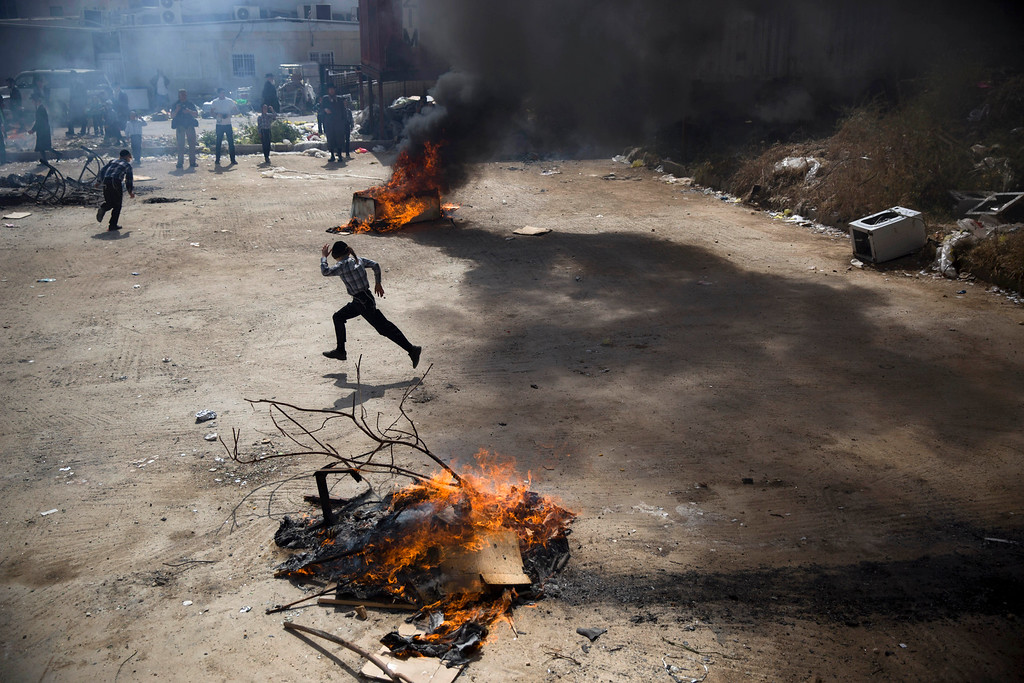 . An ultra-Orthodox Jewish boy runs between burning leavened items in final preparation for the Passover holiday in Jerusalem, Friday, April 22, 2016. Jews are forbidden to eat leavened foodstuffs during the Passover holiday that celebrates the biblical story of the Israelites\' escape from slavery and exodus from Egypt. (AP Photo/Oded Balilty)