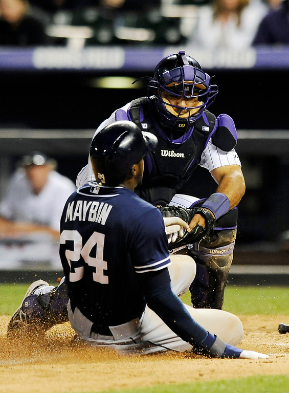 . San Diego Padres Cameron Maybin is tagged out at home by Colorado Rockies catcher Wilin Rosario in the eleventh inning of a baseball game on Thursday, June 6, 2013 in Denver. The Padres won 6-5 in 12 innings. (AP Photo/Chris Schneider)