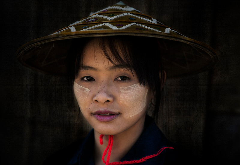 Portrait of a young woman wearing the traditional Thanaka on her face. Thanaka is a yellowish-white cosmetic paste made from ground bark. It is a distinctive feature of the culture of Myanmar, seen commonly applied to the face and sometimes the arms of women and girls, and is used to a lesser extent also by men and boys. The use of thanaka has also spread to neighbouring countries ...  Myanmar, 2017.