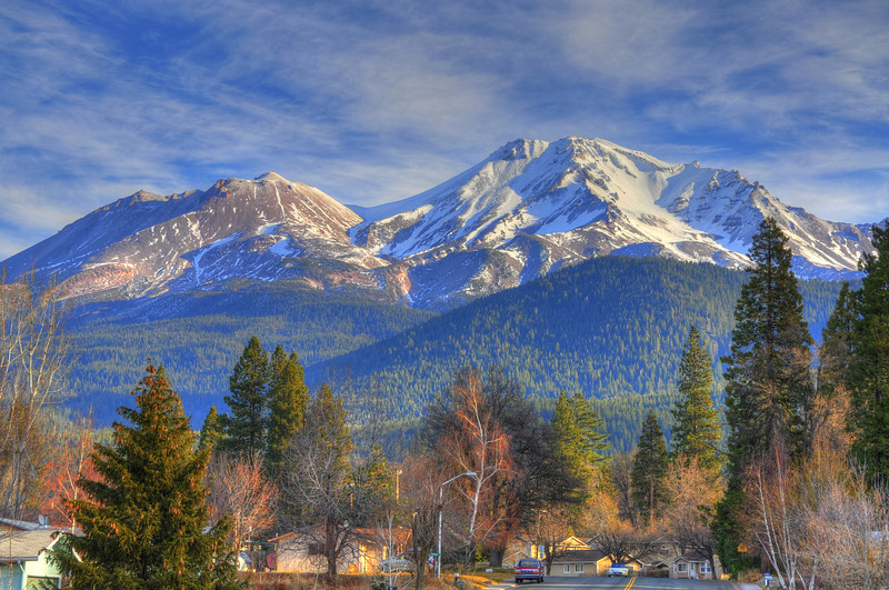 "02 Feb 12.   We leave the Mt Shasta area today with one last parting image. This one is a fun image, HDR in format, that I made to amplify the strange condition in which we found ourselves on the trip south, namely, no winter weather, with temps in the mid to high 70s. This was taken on the morning of our second day; I pulled the SUV over to the curb side on a local street in Shasta City, got out, and walking to the middle of the street, snapped this view. Note that it looks like late autumn with plenty of trees still sporting colorful leaves. A little over a week later this little community was totally snow bound with virtually no way in or out for a couple of days save for one main road. We were having breakfast just a couple miles north of here during that storm and ""kinda"" overheard a lot of the locals discussing the present conditions (refer back to the photo of the trucks). General consensus seemed to be that this was more of what they had been expecting for several weeks and that it was very needed. Based on what we saw on that second day of the southern leg,, I believe they were most correct, as the ski slopes we observed were nothing but dirt and ground cover. By now everyone should be happy as it would seem that winter has finally arrived. Regardless of the season, this must be a hard place to have to live.  ISO 320; 1/320 sec (middle of 5) @ f / 9."
