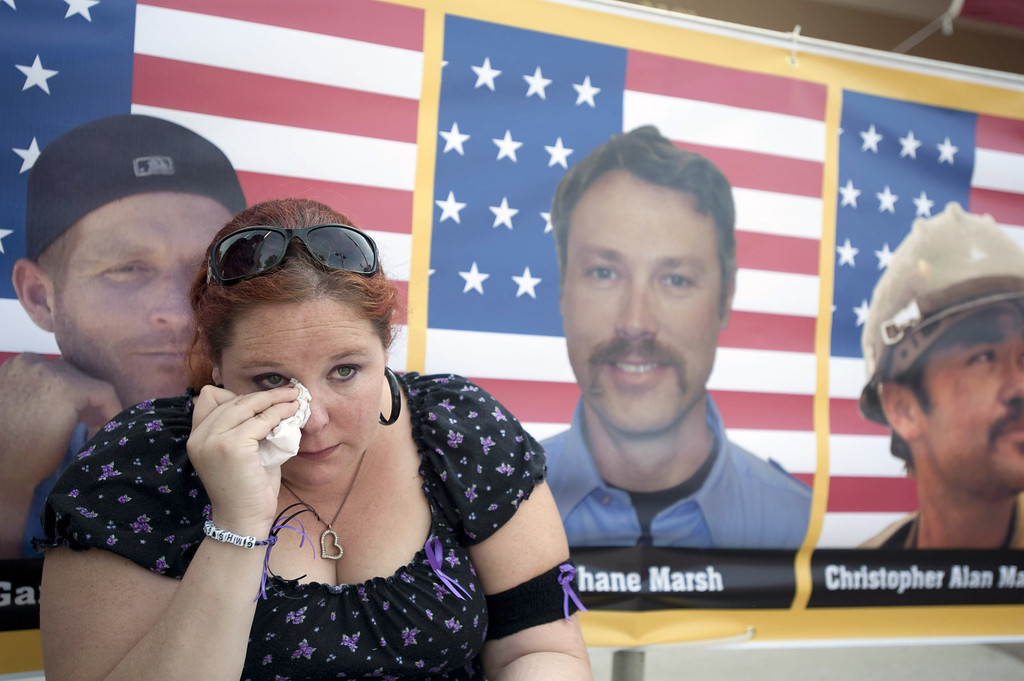 . Laura Marshall, 29, of Phoenix, Arizona sits in front of a photograph of her cousin, Garret Zuppiger (L) who was one of the 19 firefighters killed in a wildfire, at the entrance to a memorial service in their honor at Tim\'s Toyota Center July 9, 2013 in Prescott Valley, Arizona. (Photo by Laura Segall/Getty Images)