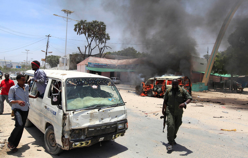 . A policeman runs away from the scene of an explosion near the presidential palace in Mogadishu March 18, 2013. A car bomb exploded near the presidential palace in the Somali capital Mogadishu on Monday, killing at least 10 people in a blast that appeared to target senior government officials, police said. REUTERS/Feisal Omar