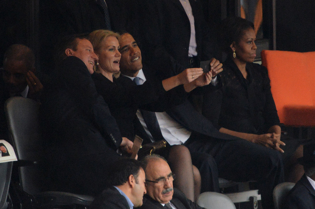 . US President  Barack Obama (R) and British Prime Minister David Cameron pose for a picture with Denmark\'s Prime Minister Helle Thorning Schmidt (C) next to US First Lady Michelle Obama (R) during the memorial service of South African former president Nelson Mandela at the FNB Stadium (Soccer City) in Johannesburg on December 10, 2013. Mandela, the revered icon of the anti-apartheid struggle in South Africa and one of the towering political figures of the 20th century, died in Johannesburg on December 5 at age 95.  ROBERTO SCHMIDT/AFP/Getty Images
